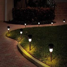 Компактные светильники вдоль бордюра дорожки