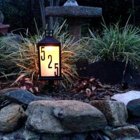 Маленький фонарик на садовой клумбе