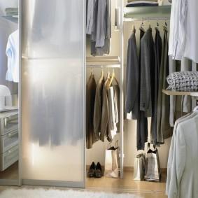 Мужская одежда на вешалках в гардеробной