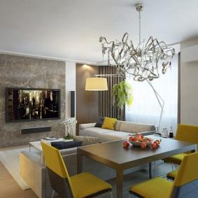 Желтые стулья в обеденной зоне столовой-гостиной