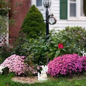 Садовый фонарь с барометром на клумбе