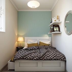 Круглое зеркало на стене узкой спальни