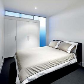 Широкая кровать в комнате без окон