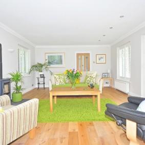 Зеленый ковер в комнате с небольшими окнами