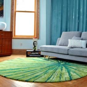Круглый коврик перед серым диваном