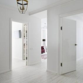 Белые двери в коридоре без мебели