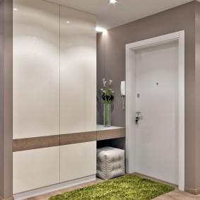 Зеленый коврик перед дверью в коридоре