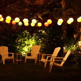 Гирлянда из фонариков над садовыми креслами