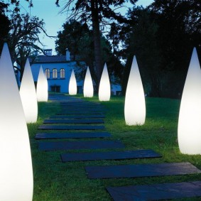 Конусовидные светильники вдоль тропинки из камня