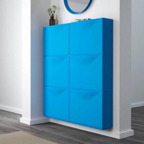 Синий шкафчик на стене прихожей