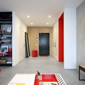 Красный пуф в прихожей квартиры студии