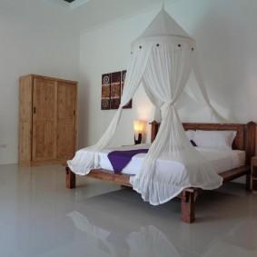 Белый балдахин над кроватью женщины