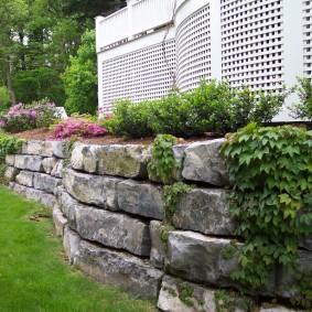 Решетчатый забор над подпорной стенкой из камня