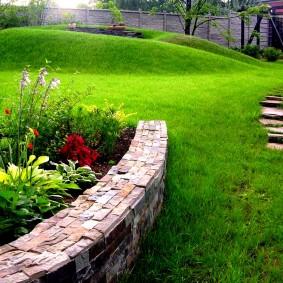 Зеленый газон на участке с рельефом