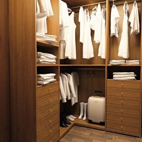 Белые рубашки на вешалках в шкафу