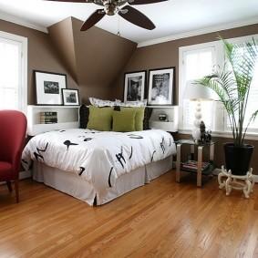 Кровать в углу комнаты с большими окнами