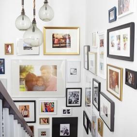 Фото в разных рамках в углу лестничного пролета