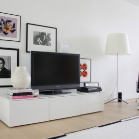 Черный телевизор на белой тумбе