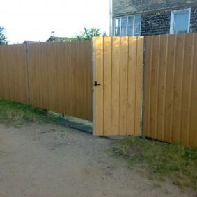 Открытая калитка в заборе загородного участка