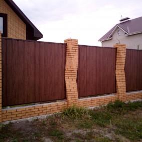Кирпичные столбы с изгибом на дачном заборе