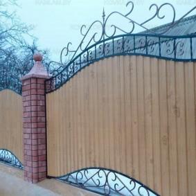 Кованный забор на кирпичных столбах