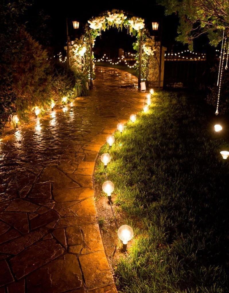 Цепочка низких светильников вдоль дорожки к калитке