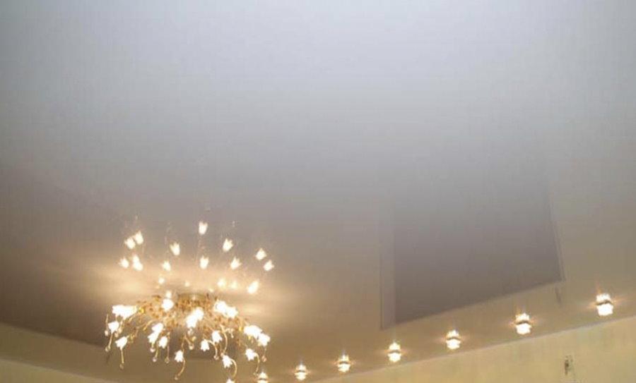 Люстра на потолке гостиной с глянцевым полотном