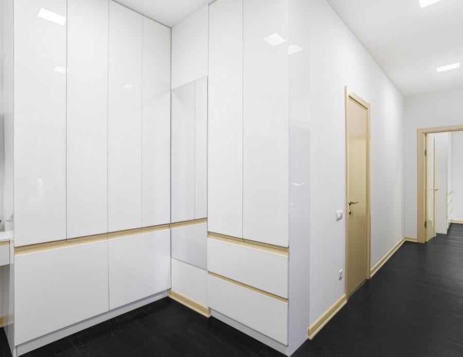 Белая мебель в коридоре с темным полом