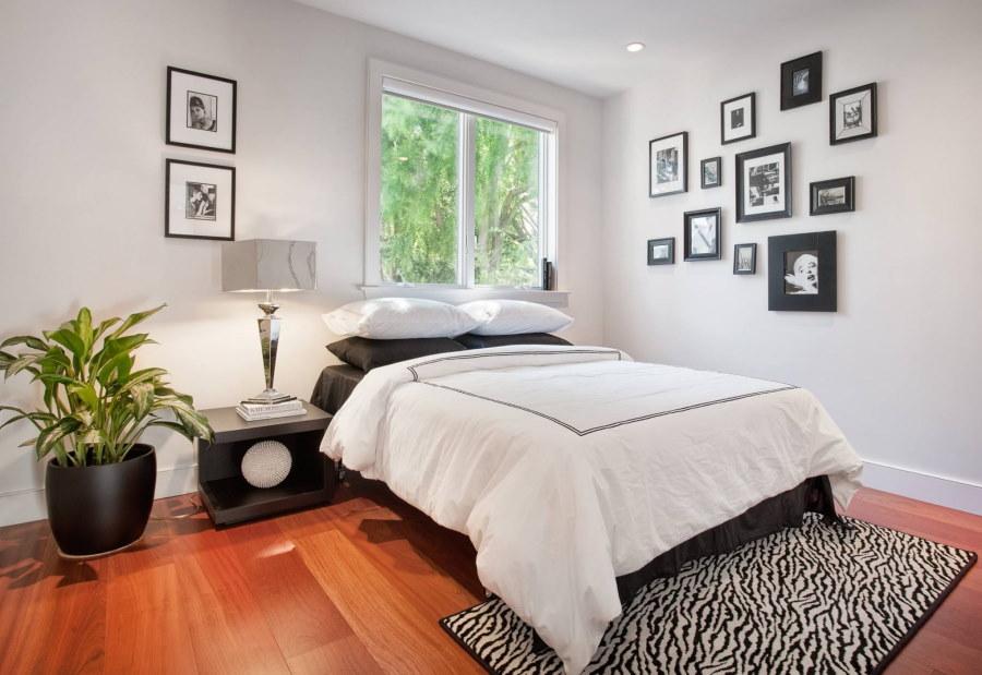 Асимметричное размещение фотографий в интерьере спальной комнаты