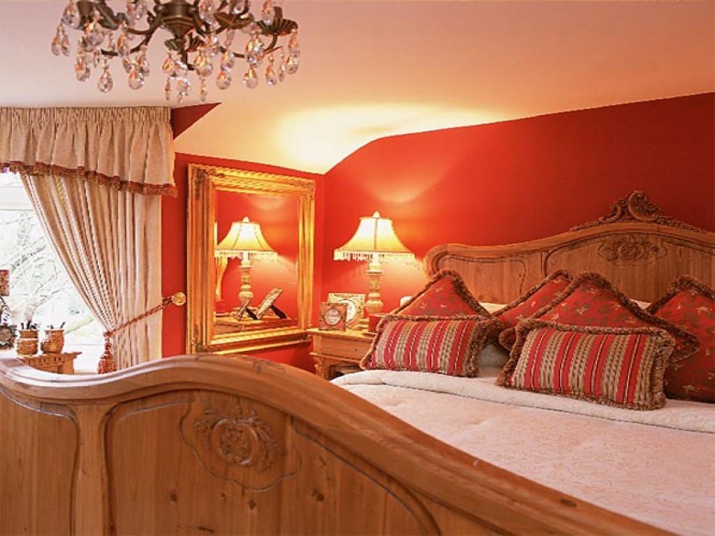 Деревянная кровать в спальне с позолотой на зеркале