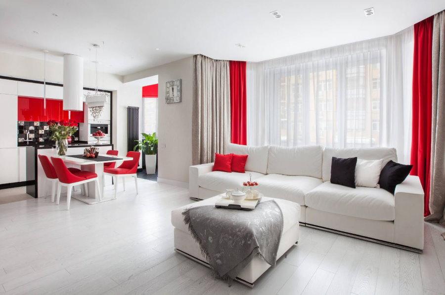 Акценты красного цвета в интерьере белой кухни-гостиной