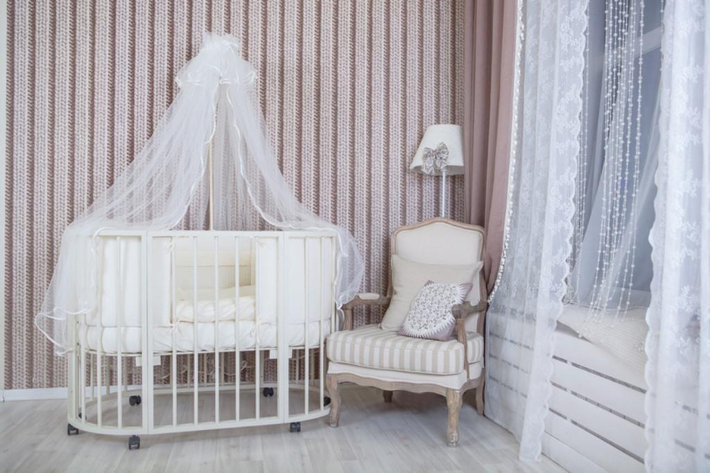 круглая детская кроватка в комнате