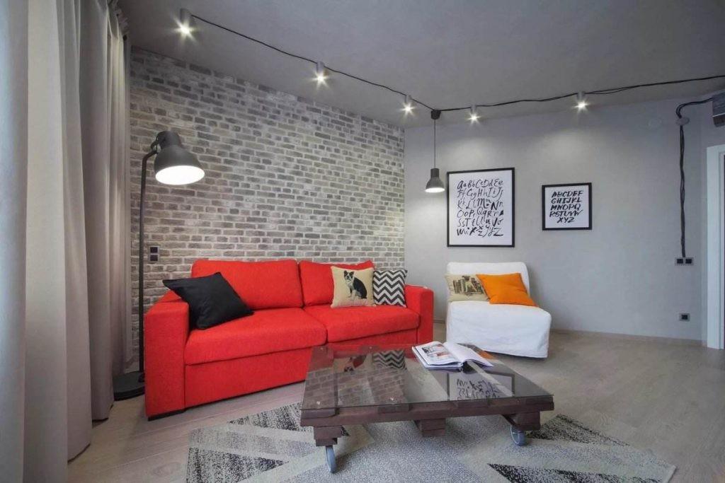 Красный раскладной диван в серой комнате