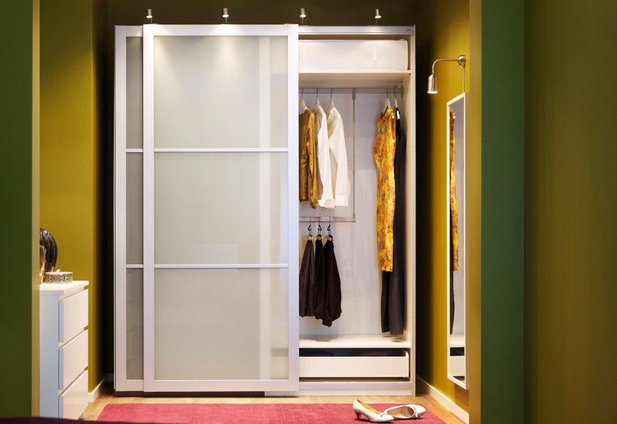 Одежда на вешалке в шкафу купейного типа