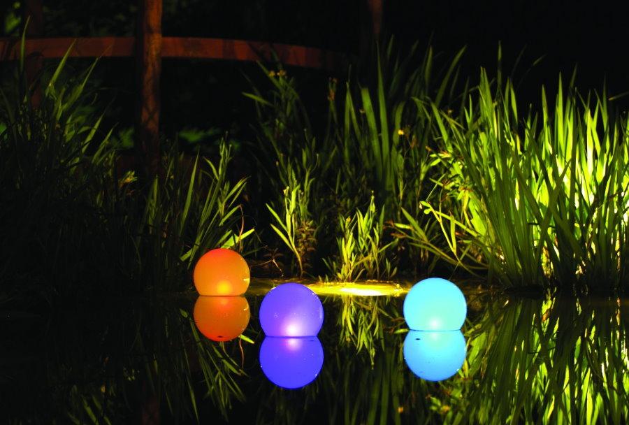 Разноцветные плавающие фонарики на поверхности пруда