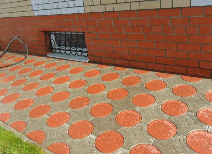 Красная круглая плитка на отмостке перед домом