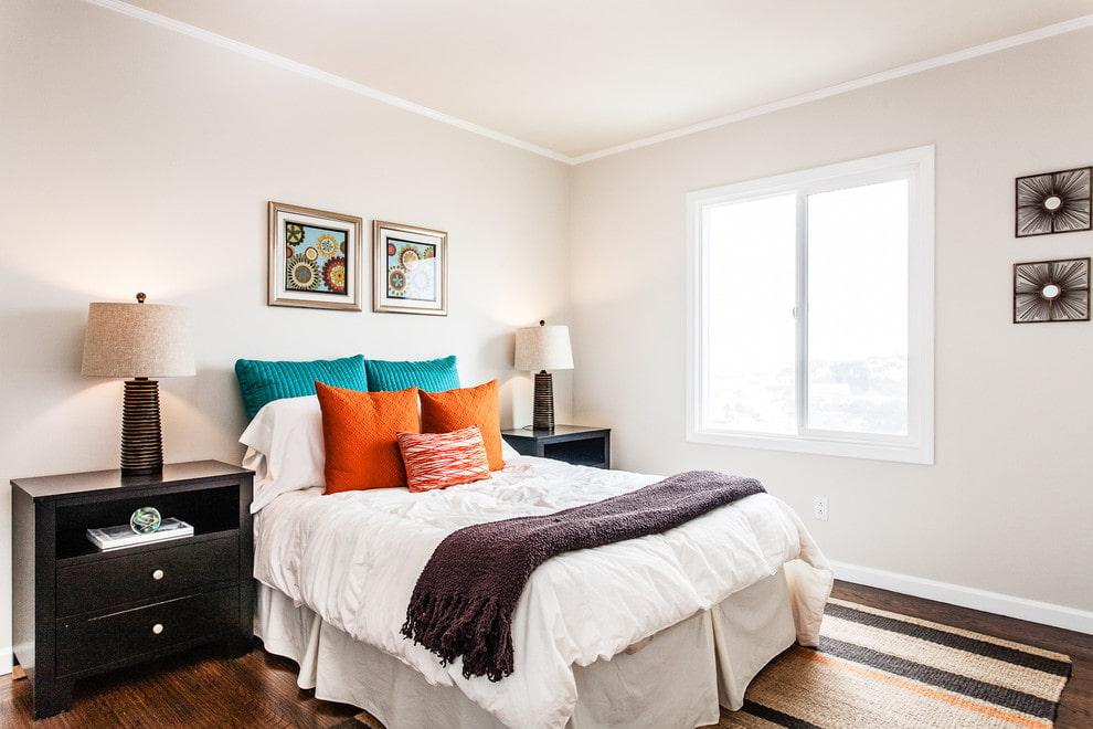 Яркие подушки в белой спальной комнате