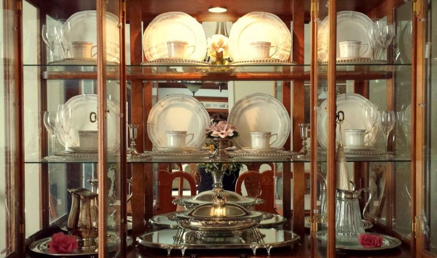 Чайный сервиз на полках стеклянной витрины в зале