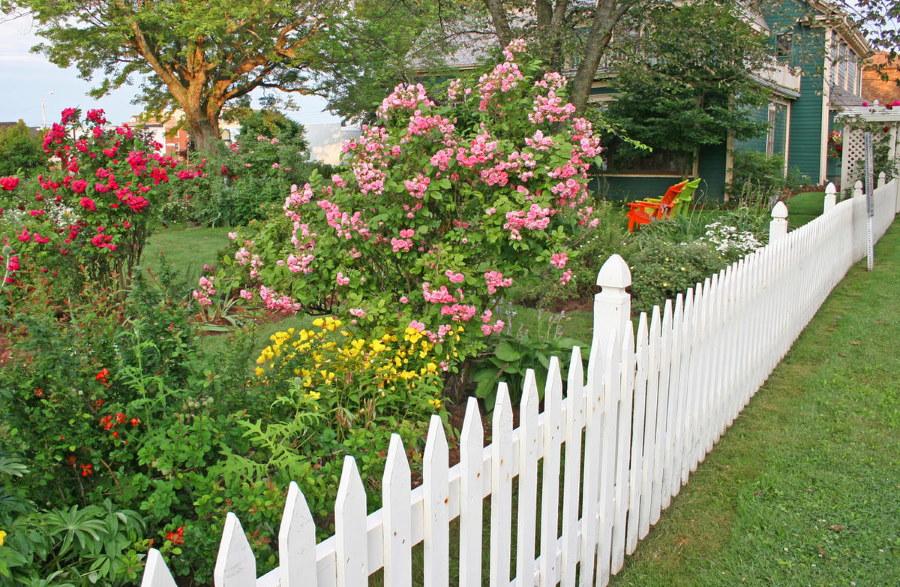 Оформление цветника в палисаднике с белым забором
