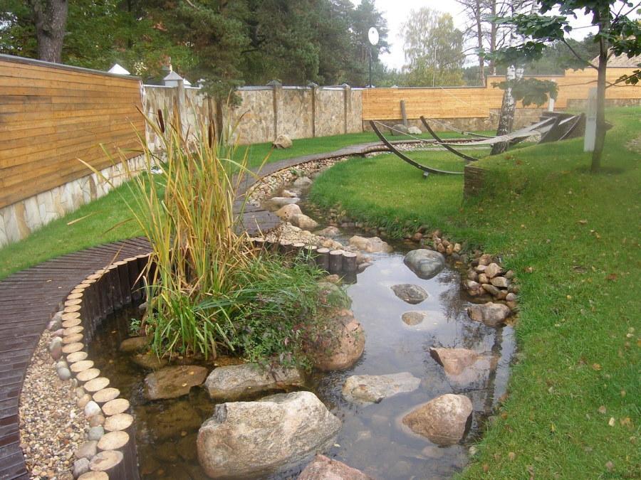 Искусственный ручей вдоль забора на садовом участке