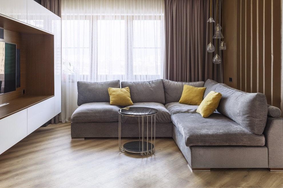 серый диван у окна в гостиной