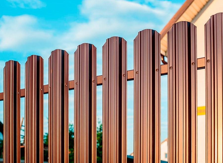 Крепление заклепками металлического штакетника на заборе
