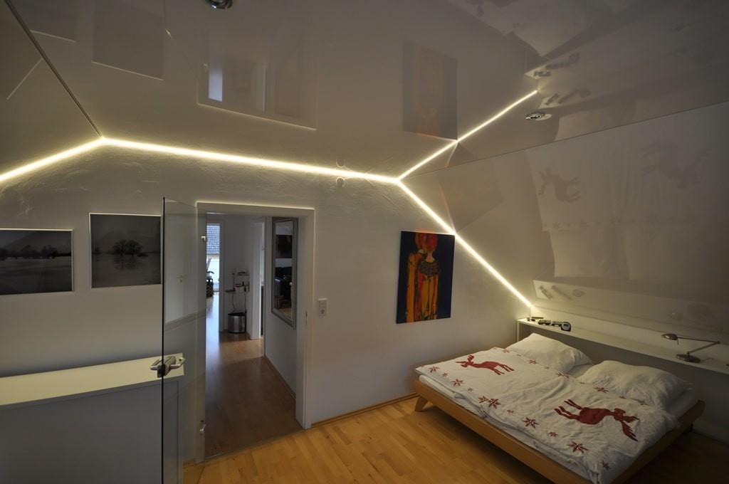 Скошенный натяжной потолок в мансардной комнате