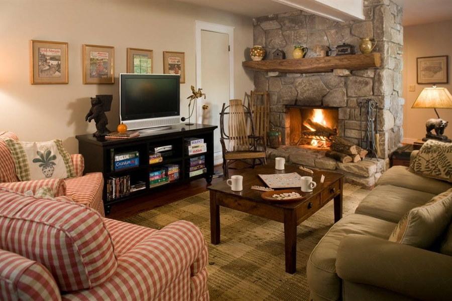 Телевизор на черной тумбе в гостиной с дровяным камином