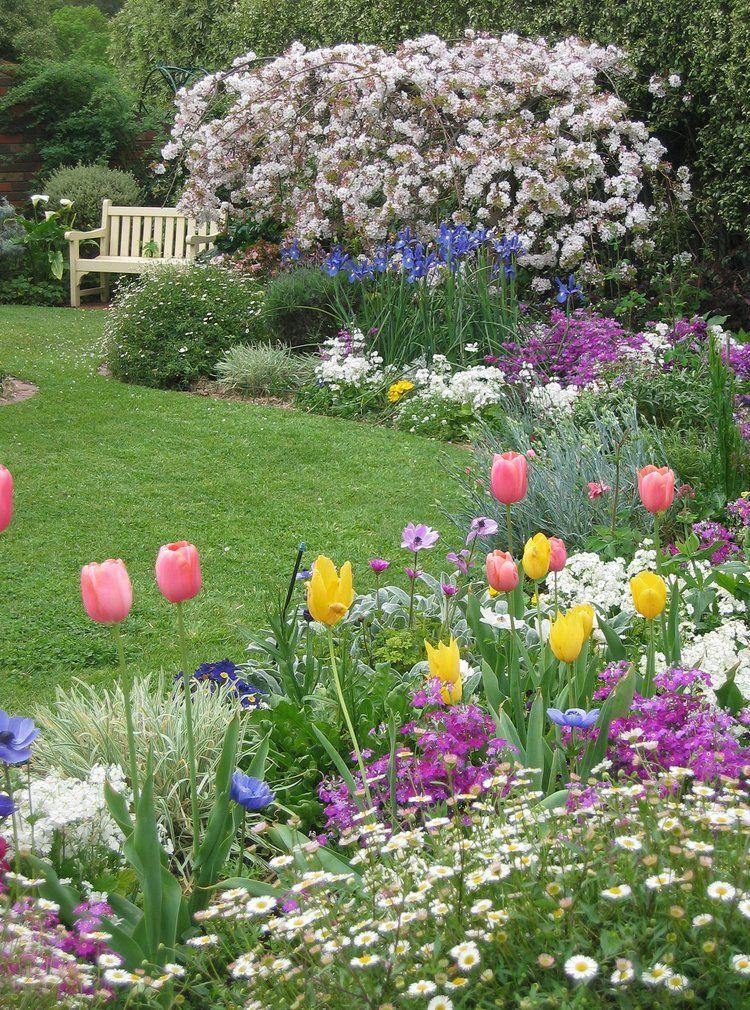 Садовая клумба с тюльпанами и другими цветами