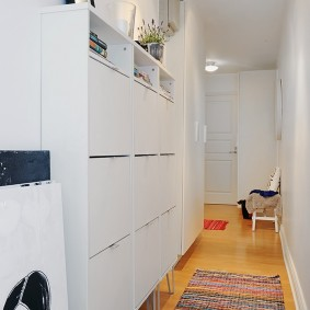 Пестрый коврик на полу прихожей с белой мебелью
