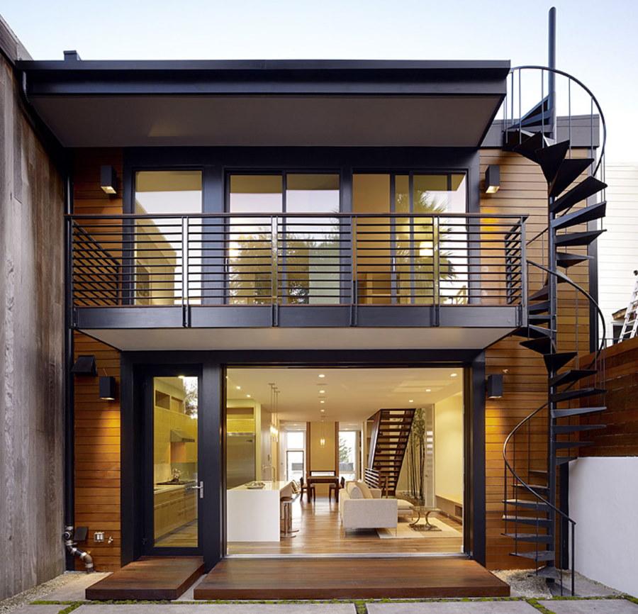 Винтовая лестница из металла на фасаде дома с балконом