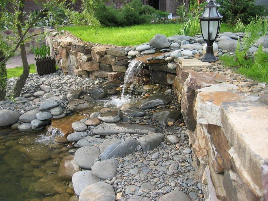 Садовый фонарь возле водопада из камней