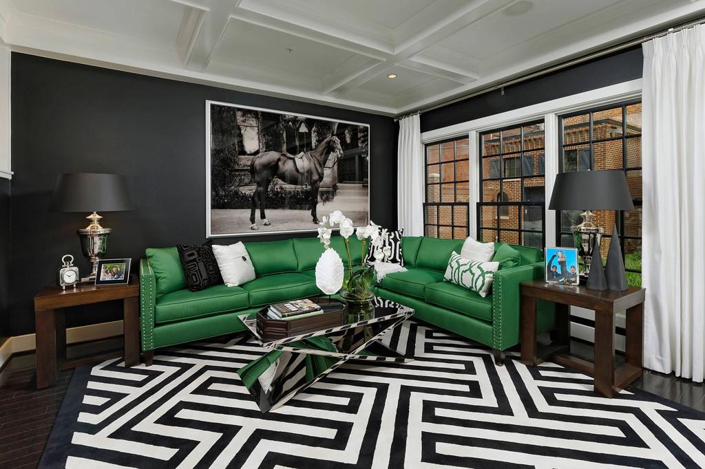 Кожаный диван зеленого цвета в зале с черной стеной