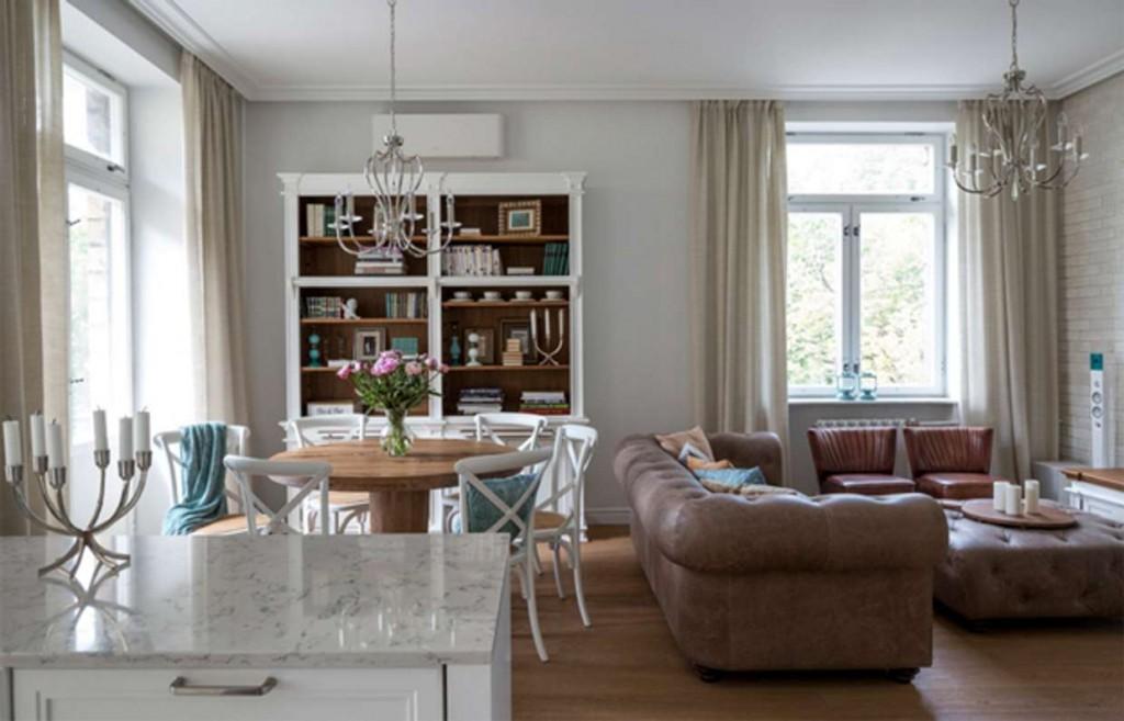 Кожаный диван посередине гостиной-столовой